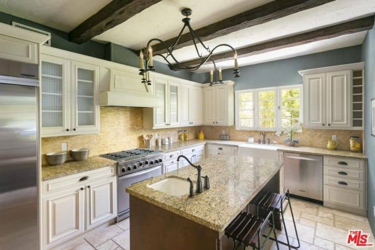 Inset appliances and white cabinetry surround a granite top island lighted by a candle chandelier that hung from the wood beam ceiling. This kitchen has limestone flooring and white framed windows that invite natural light in.