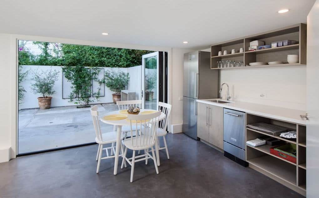 This kitchenette offers white dining set along with light wood cabinets and shelves that are fixed against the white walls. It has concrete flooring and glazed folding doors that open to the courtyard.