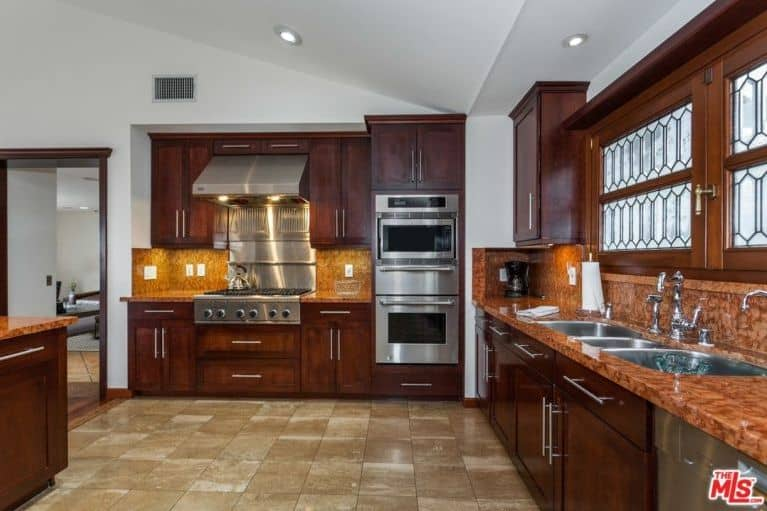 Spacious kitchen with dark wood cabinetry and marble countertops extending to the backsplash. It is equipped with stainless steel appliances and undermount sinks that are paired with chrome fixtures.