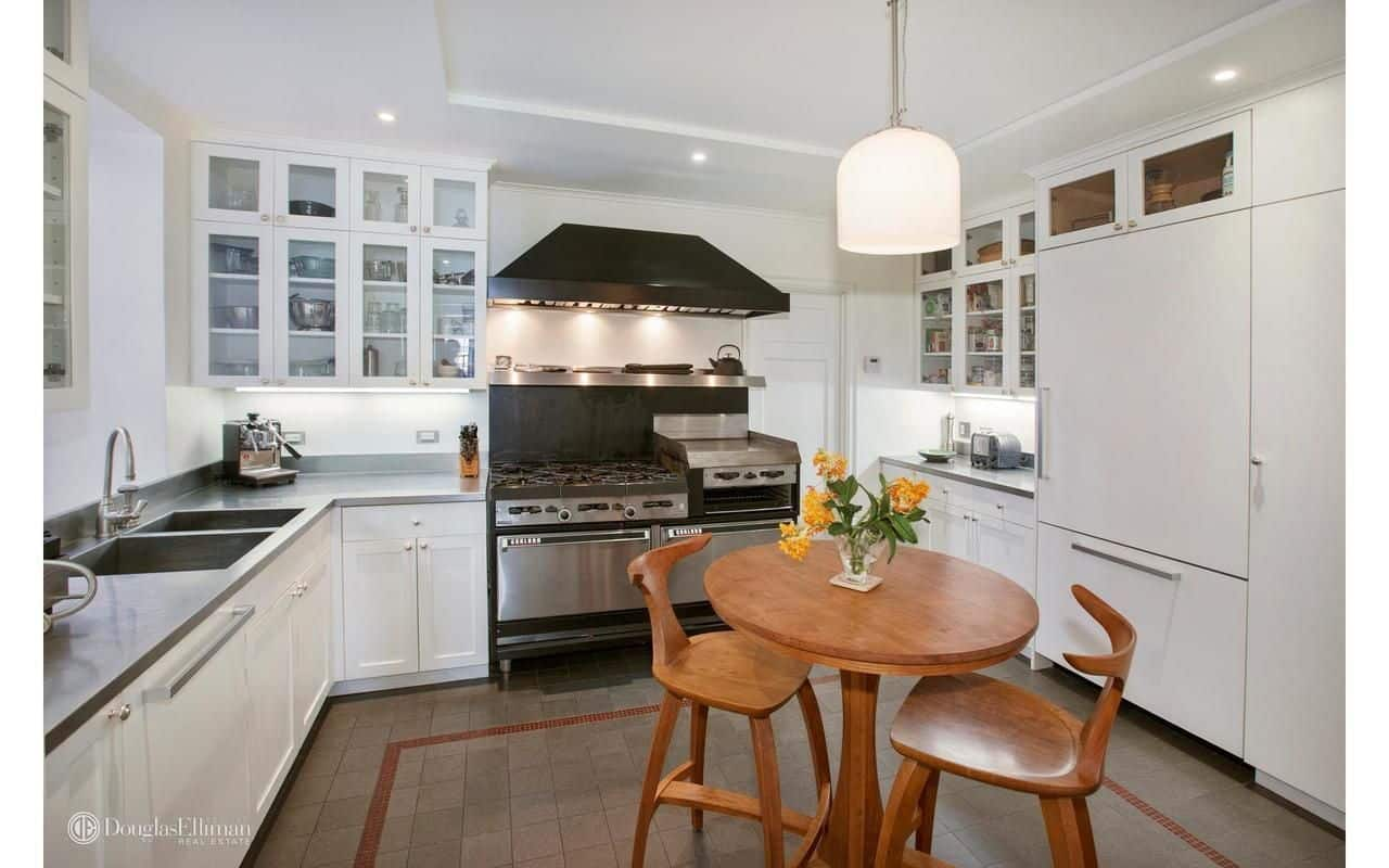 White cabinetry fades into the white walls in this kitchen with multi-colored appliances and wooden dining set over tiled flooring. It is illuminated by recessed lights and a glass dome pendant that hung from the tray ceiling.