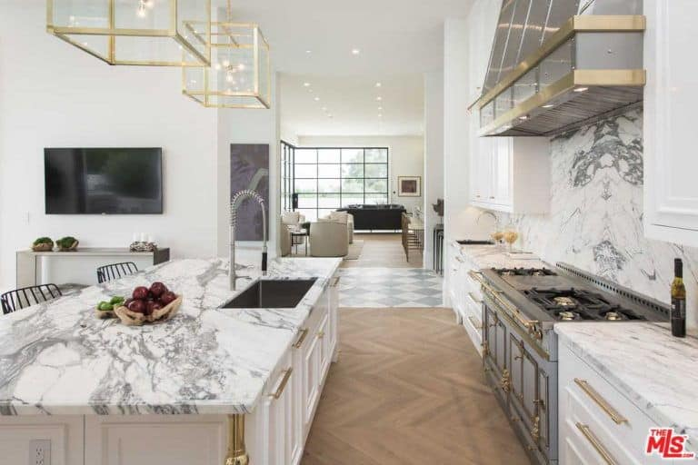 Cube glass pendants hang over the white central island that's fitted with an undermount sink and a chrome faucet with a pull-down sprayer. This kitchen boasts marble countertops and backsplash along with white cabinets that are accented with brass hardware.