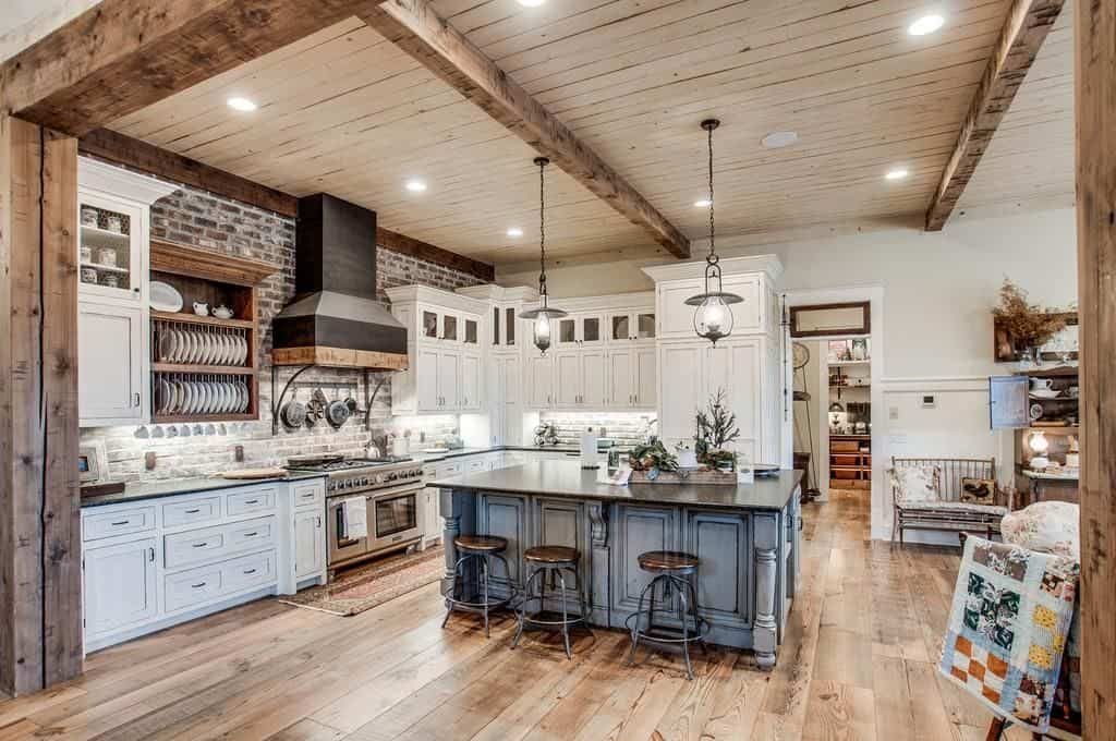 This kitchen showcases white cabinetry and a contrasting black vent hood that's fixed against the brick wall. There's a blue island with granite countertop in the middle that's illuminated by glass pendants hanging from the wood beam ceiling.