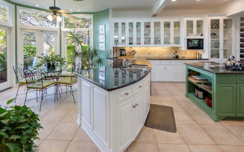 This eat-in kitchen offers an ornate dining set, a curved peninsula and a green island over beige tiled flooring topped by a brown rug. It includes white and glass front cabinets along with black appliances that match the granite countertops.