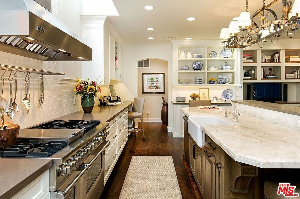 A stainless steel pot rack integrated with lamps hang over a raised island that's fitted with a farmhouse sink and chrome fixtures. It is complemented by white cabinetry and a jute rug that lays on the dark hardwood flooring.