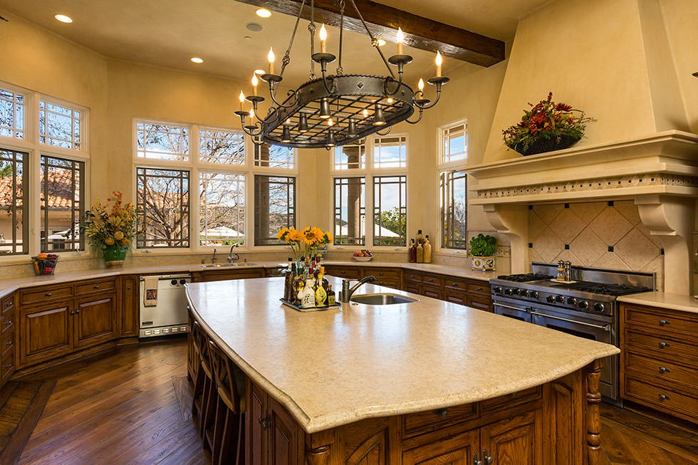 Warm kitchen with natural wood cabinets and a matching granite top island that blends in with the hardwood flooring. It is illuminated by candle lamps on an oval pot rack along with natural light from the glazed windows.