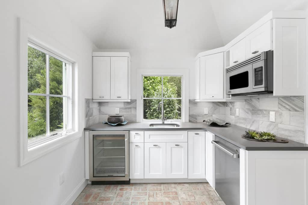This kitchen boasts gray tile backsplash matching with the appliances and countertop along with white cabinets that fade into the white walls. It has rustic <a class=