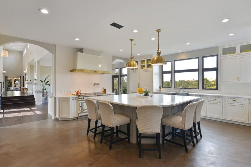 Upholstered round back chairs surround the central island that's lighted by a pair of brass pendants. It is accompanied by white appliances and cabinets that are accented with gold hardware.