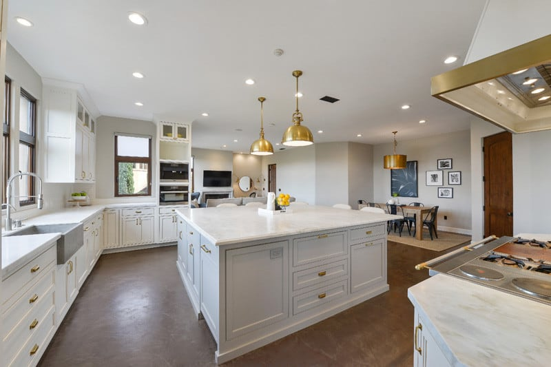 Brass pulls and pendant lights stand out in this white kitchen with matching cabinets and island topped with a gray farmhouse sink and marble countertops. There's a cozy dining set on the side that's highlighted by gallery frames.