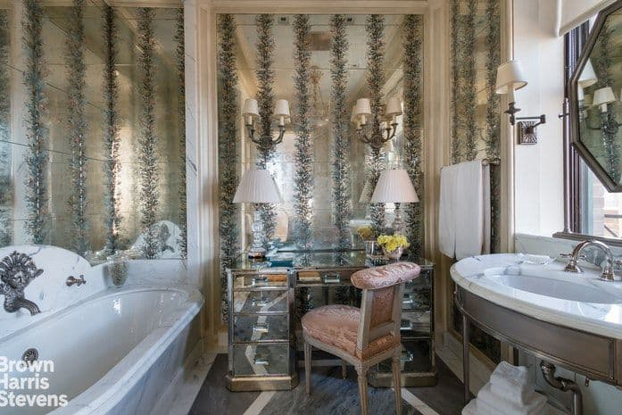 A sleek vanity paired with a cushioned chair blends in with the stylish mirrored walls mounted with traditional sconces. This master bathroom offers a deep soaking tub and a marble top washstand under the octagonal mirror.