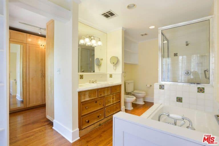 The warm master bathroom boasts a deep soaking tub and a walk-in shower facing the traditional toilets against the beige walls. It includes a marble top vanity fitted with wooden drawers that blend in with the rich hardwood flooring.
