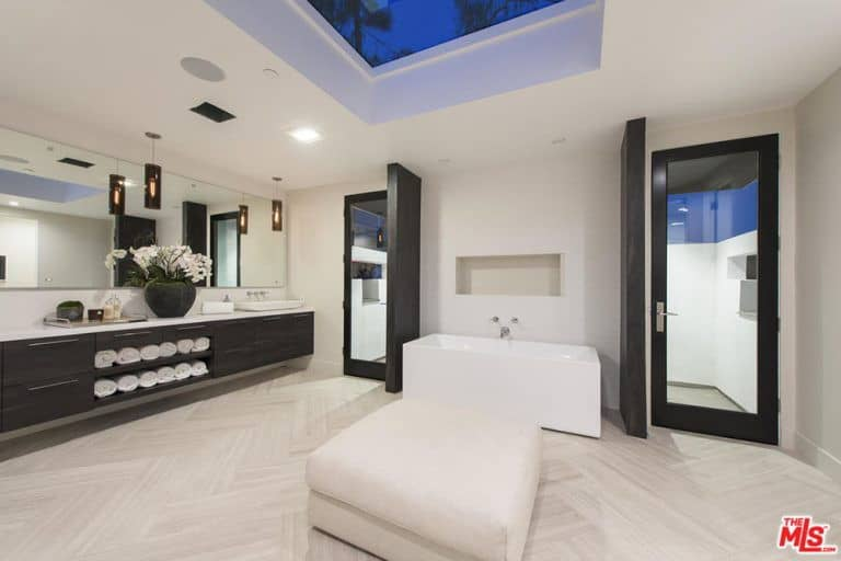 The sleek master bathroom features a floating vanity under the frameless mirror along with a freestanding tub that's complemented by a white ottoman. It has chevron flooring and a tray ceiling fitted with a skylight.
