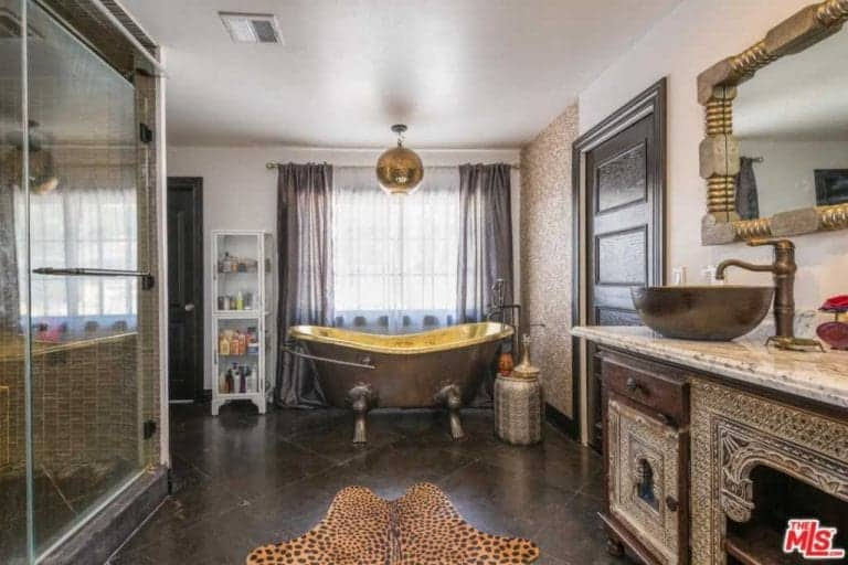 Sophisticated master bathroom with a walk-in shower and a clawfoot tub by the glazed window illuminated by a gold chandelier. It includes a vessel sink vanity and a leopard rug that lays on the tiled flooring.