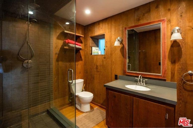 Cozy master bathroom with a walk-in shower and a traditional toilet facing the wooden vanity that's paired with a framed mirror. It includes chrome sconces and a small window adjacent to the floating shelves mounted on the wood paneled wall.