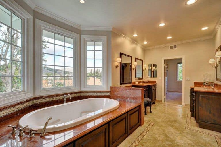 Recessed ceiling lights and traditional sconces add warmth in this master bathroom with a deep soaking tub and wooden vanities paired with a cushioned chair.