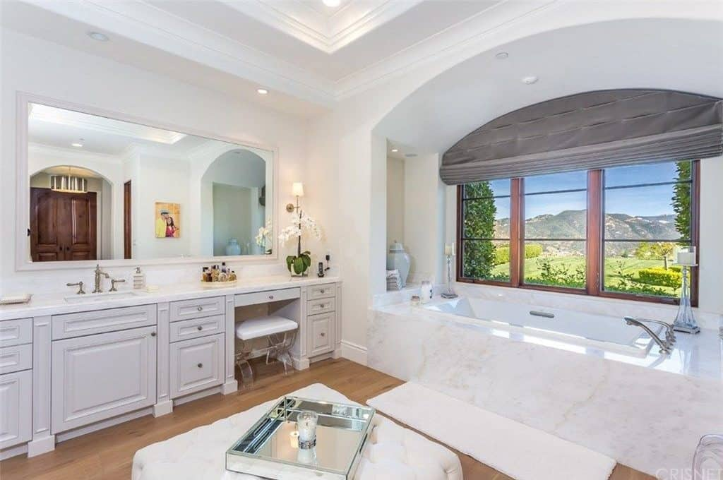 White master bathroom with marble top vanity and an alcove tub by the glazed windows framing a breathtaking mountain view. It includes a tufted ottoman and a white runner that lays on the light hardwood flooring.