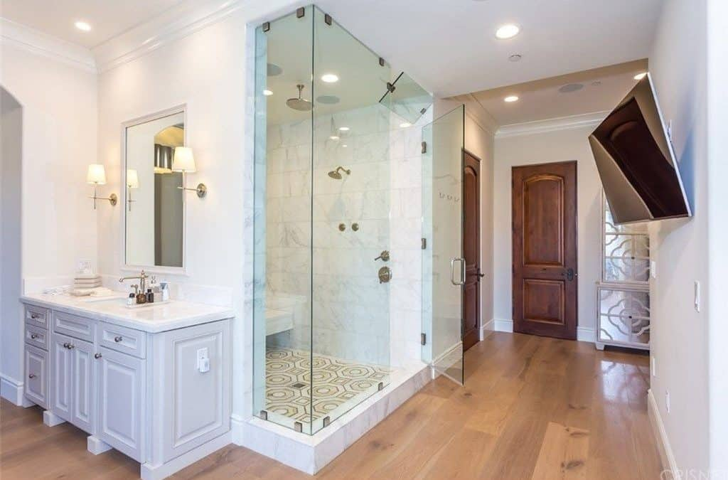 This master bathroom offers a single sink vanity paired with a white framed mirror along with a wall-mount TV facing the walk-in shower that's enclosed in frameless glass panels.