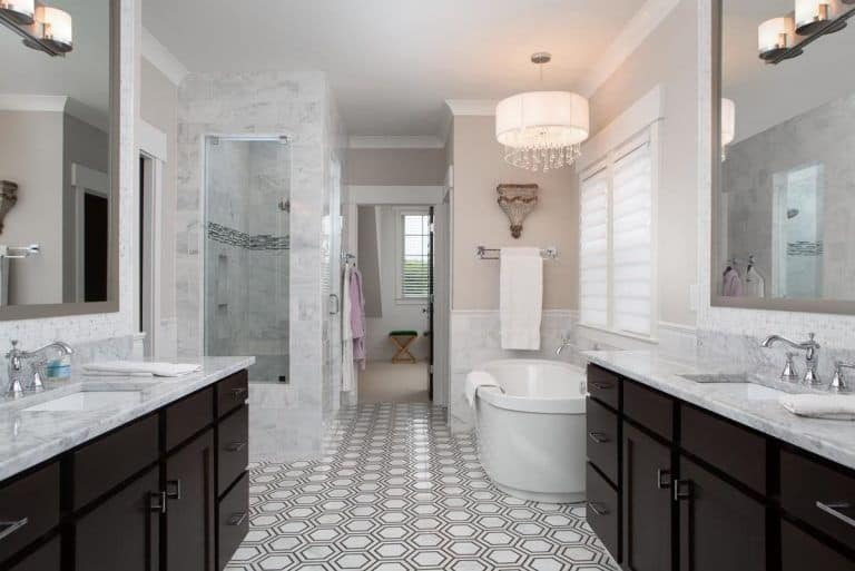 A fancy drum chandelier illuminates the freestanding tub by the glazed window covered in translucent blinds. It is accompanied by a walk-in shower and facing black vanities with marble countertops.