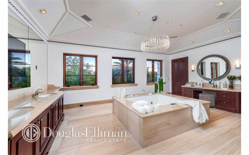 Large master bathroom boasts dark wood vanities and a deep soaking tub in the middle that blends in with the tiled flooring. It is illuminated by an eccentric glass chandelier that hung from the vaulted ceiling.