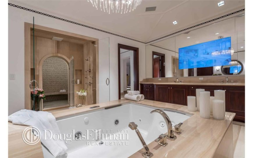 A close-up look at the deep soaking tub with chrome fixtures facing the dual sink vanity under the frameless mirrors. There's a walk-in shower on the side with an arched glass door leading to a sauna room.