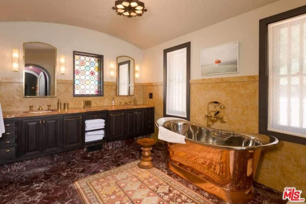 A stained glass window provides a nice accent in this master bathroom with dual sink vanity and a luxurious copper tub complemented with a printed rug. It has marble flooring and a barrel vaulted ceiling mounted with a stylish flush light.