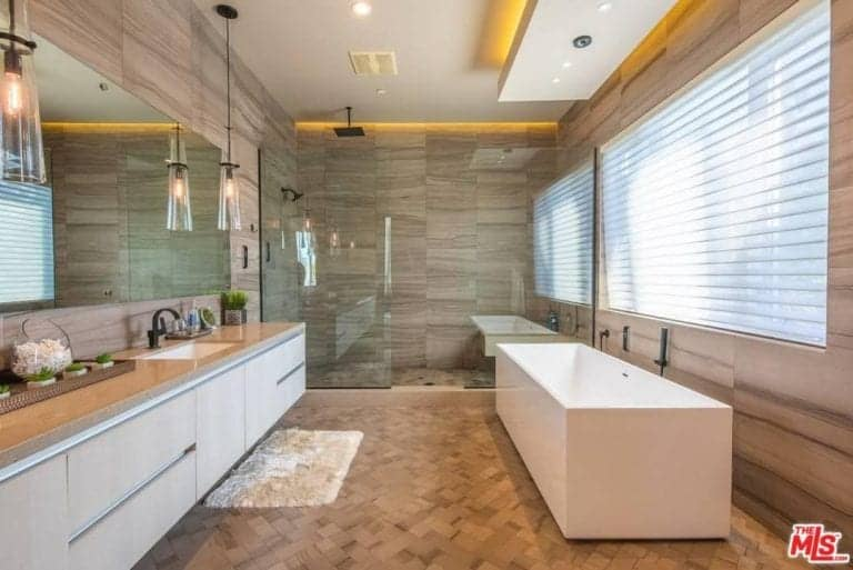 This master bathroom showcases a freestanding tub and a floating sink vanity with a beige shaggy rug on the side laying on the tiled flooring. It is completed with a spacious walk-in shower that's fitted with wrought iron fixtures.
