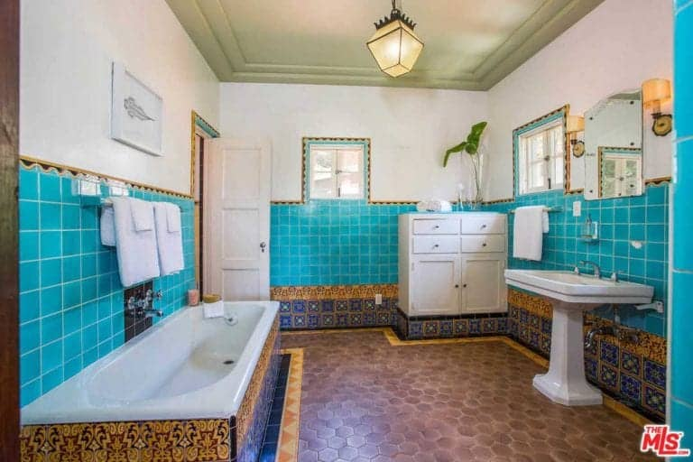 Spanish style master bathroom with brown hex tile flooring and turquoise backsplash accented by decorative tiles. It is completed with a drop-in tub and a pedestal sink that's paired with a frameless mirror.