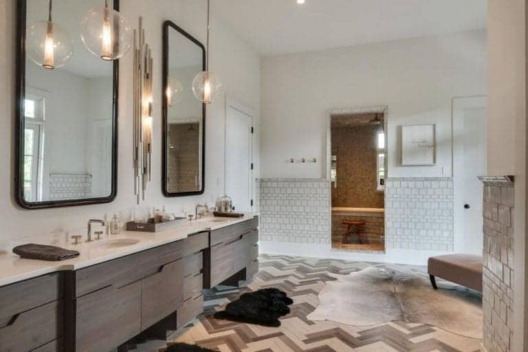 Glass globe pendants hang over the natural wood vanity with dual sink and black framed mirrors mounted on the white wall. It is complemented by cowhide rugs that lay on tiled flooring arranged in a herringbone pattern.