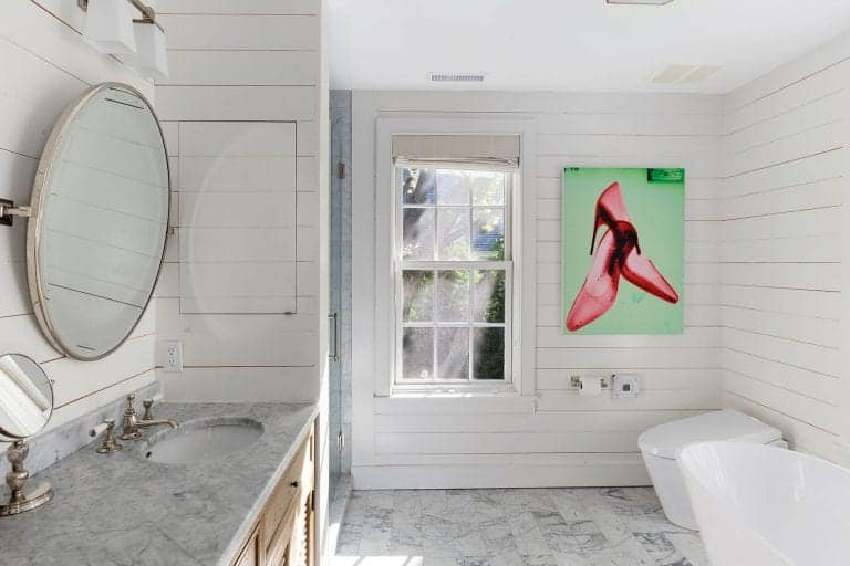 A gorgeous artwork brings a pop of color in this white master bathroom with shiplap walls and tiled flooring matching with the marble countertop. It is completed with a modern toilet and a wooden vanity that's paired with a round mirror.