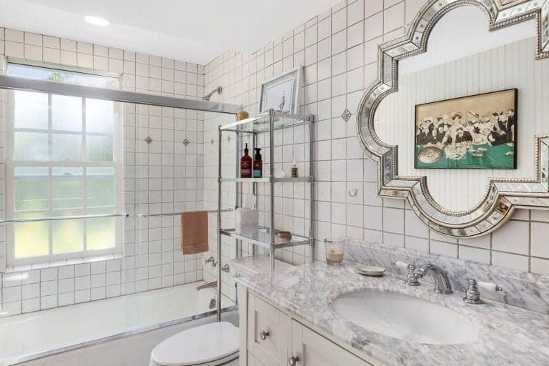 Shower and tub combo along with a marble top vanity flank the toilet with a stainless steel shelving unit on top. This room is decorated with a stylish chrome framed mirror reflecting a black framed artwork that's mounted on the beadboard wall.