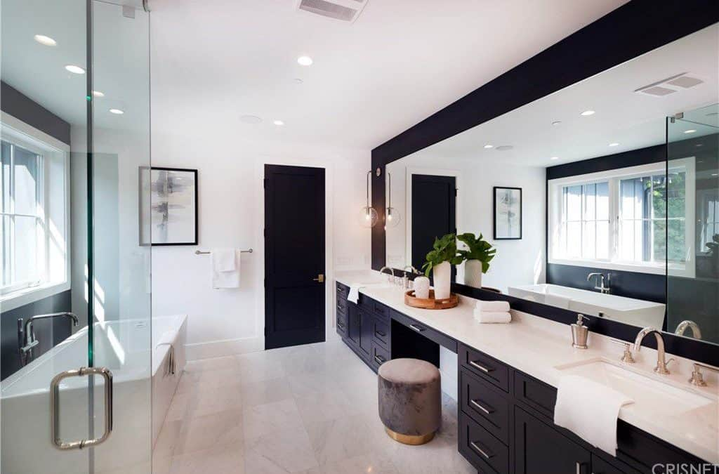 Black and white master bathroom with a freestanding tub and a dual sink vanity paired with a round velvet ottoman. It is illuminated by recessed ceiling lights along with natural light flowing in from the white framed windows.