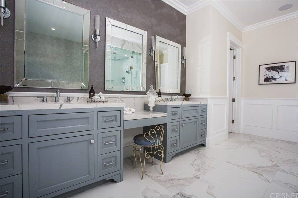 A closeup look at the dual sink vanity with white marble countertops matching with the tiled flooring. It is complemented by an ornate metal chair and chrome framed mirrors flanked by cylindrical sconces.