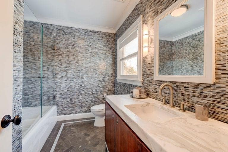 Linear mosaic tiles run throughout this master bathroom offering a tub and shower combo along with a toilet and marble top vanity under a white framed mirror.