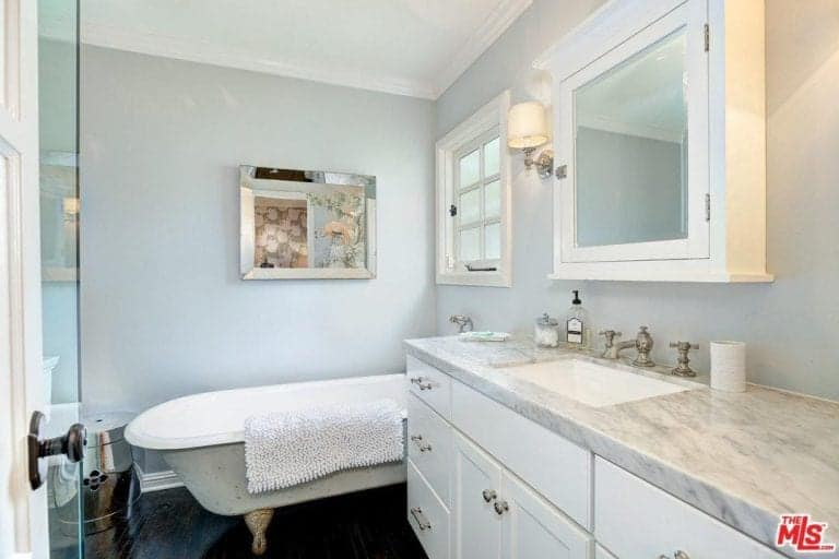 This master bathroom showcases a clawfoot tub and a marble top vanity paired with a medicine cabinet. It is decorated with a chrome framed mirror mounted on the white wall.
