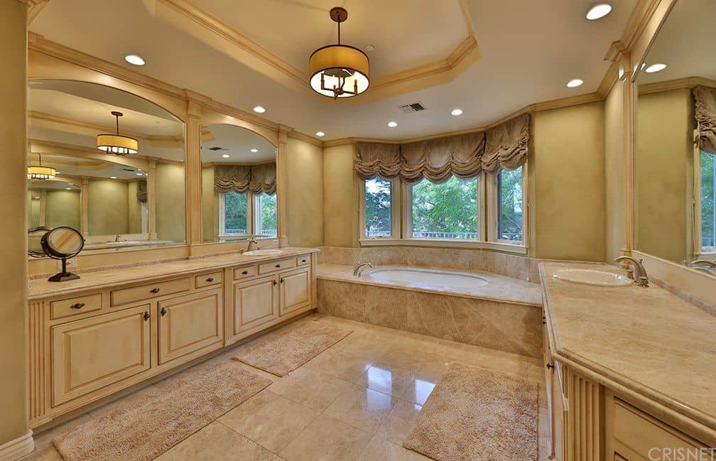 Warm master bathroom with a tray ceiling and beige tiled flooring matching with the marble countertops and bathtub surround by the bay window dressed in a classy roman shade. It includes shaggy rugs and facing vanities with arched mirrors.