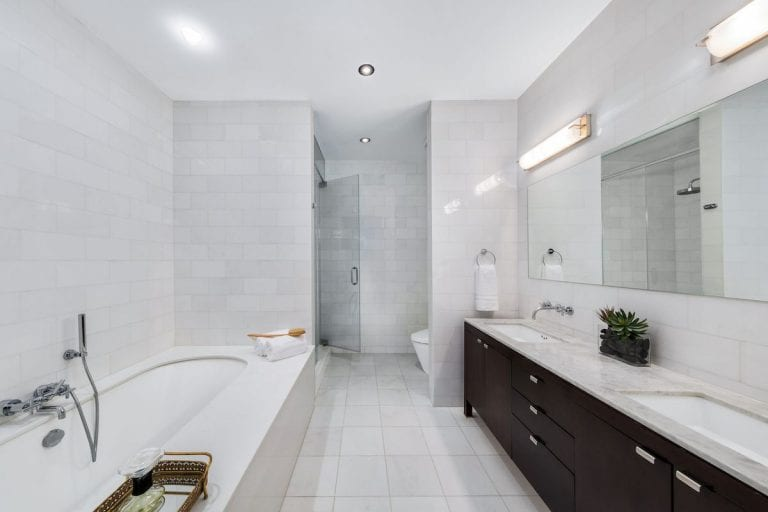 The bright master bathroom features a drop-in tub and a black vanity with dual sink and a frameless mirror illuminated by linear sconces. It is completed with a walk-in shower and a toilet concealed in a white brick wall.