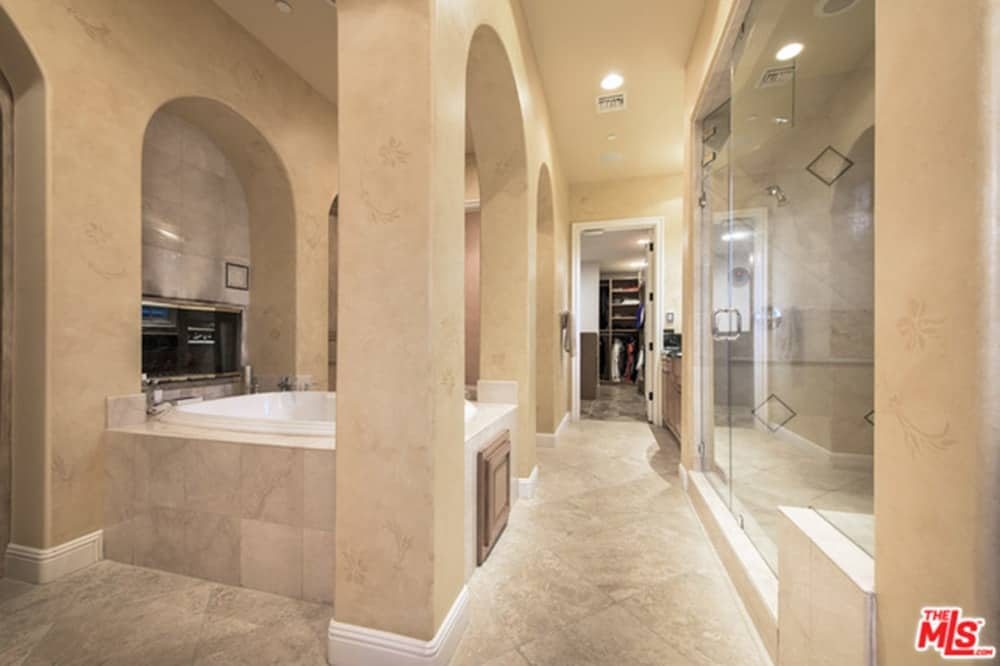 Mediterranean master bathroom with a large shower area and a deep soaking tub framed with open arches. There's a white door at the far end that opens to the walk-in closet.