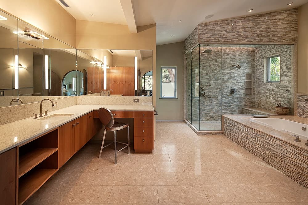 Spacious walk-in shower with linear mosaic tile backsplash matches the deep soaking tub over brick flooring. It is accompanied by a large wooden vanity that's paired with chrome round back chair.