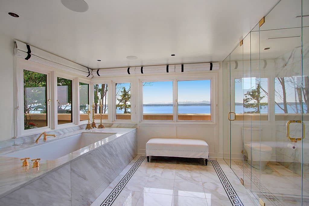 Gold fixtures and hardware provide an elegant accent to the marble bathtub and frameless glass doors housing the toilet and walk-in shower. There's a skirted ottoman by the glazed windows overlooking a stunning bay view.