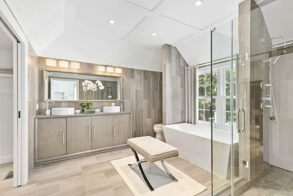 The airy master bathroom features a light wood vanity that blends in with the tiled walls and flooring. It is completed with a walk-in shower and a freestanding tub by the white framed windows complemented by a cushioned stool over a beige rug.