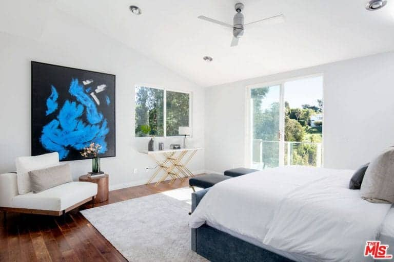 This master bedroom has a stylish wall decor and a sitting chair nearby. The room features hardwood floors topped by an area rug where the cozy bed set is situated.
