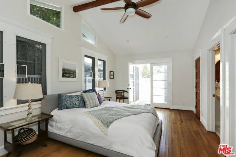 Master bedroom with a tall ceiling and hardwood floors. The room also has a large gray bed set lighted by table lamps on both sides.