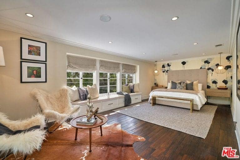 Large master bedroom featuring hardwood flooring and beige walls, along with a classy bed with built-in bedside tables and lighted by pendant lights.