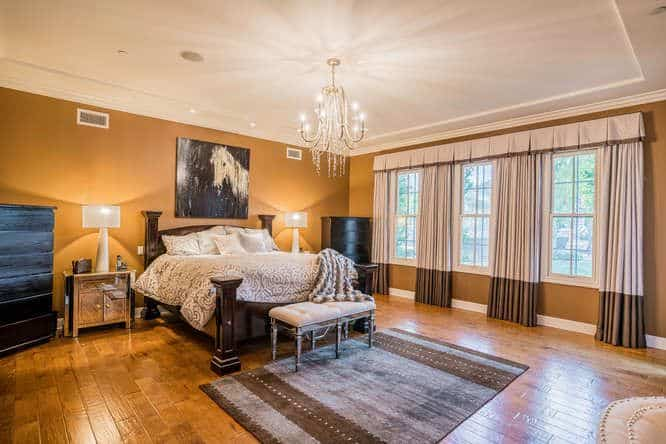 A spacious master bedroom with hardwood floors and brown walls, along with a tray ceiling lighted by a fancy chandelier. The room offers an elegant bed with table lamps on both sides.