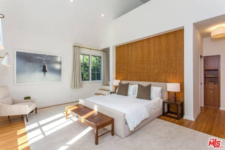 Master bedroom offering a classy bed setup lighted by table lamps on both sides. The room offers a lovely artistic wall decor and an area rug covering the hardwood flooring.