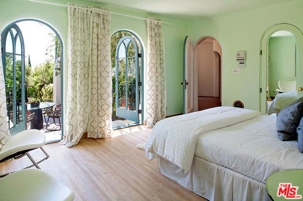 Master bedroom with a comfy bed set and has its own bathroom and closet. The room is surrounded by green walls and hardwood floors.