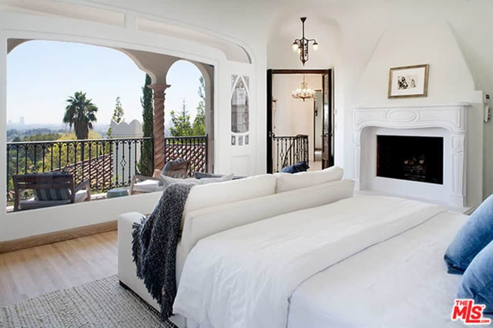 Master bedroom featuring a white bed setup and a white sofa facing the outdoor view. The room has a fireplace and a sitting area on the balcony.