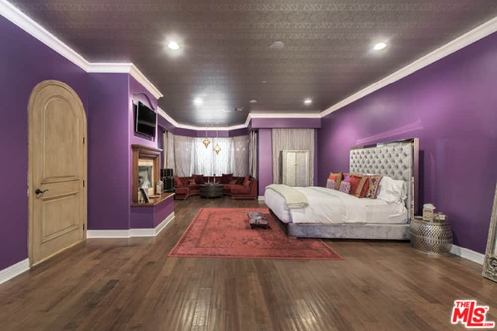 Large master bedroom featuring a gorgeous ceiling and hardwood flooring, along with purple walls. The room offers a luxurious bed and a fireplace with a TV on top, together with a personal living space on the side.