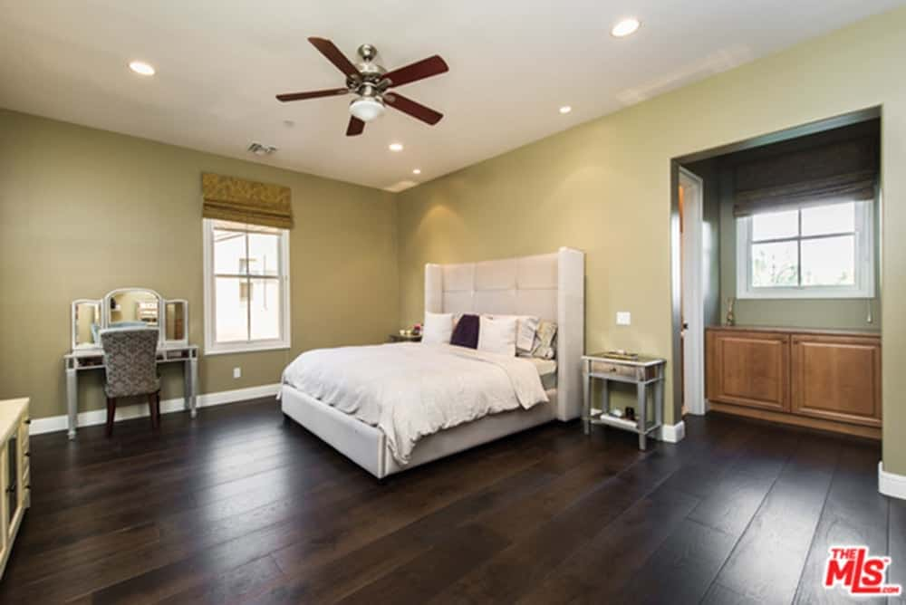 Spacious master bedroom featuring hardwood flooring. It offers a classy bed and a beautiful makeup desk on the side.