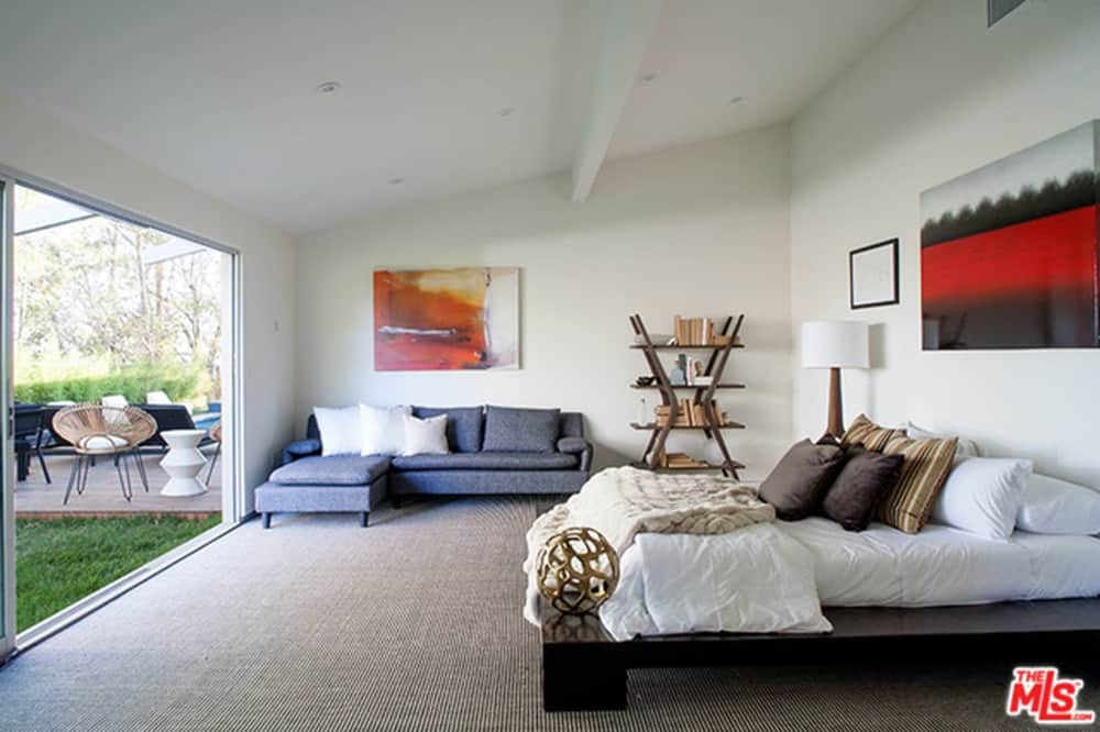 Modern master bedroom with a modish bed and a stylish blue L-shaped sofa set on the side. The room has a doorway leading to the home's garden.