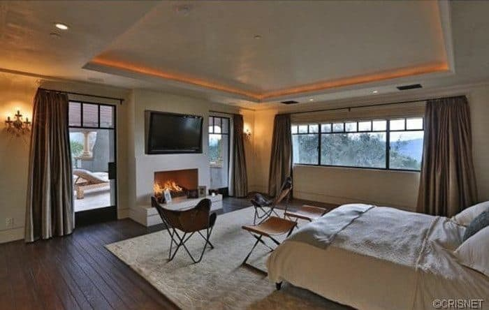 Spacious master bedroom with hardwood floors and a tray ceiling. The room has a fireplace and a large widescreen TV on top of it.